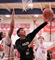 Abilene High's Joe Joe Escobedo (4) drives to the basket against Cooper's Noah Garcia, left, and Ashton Curtis. Cooper won the game 78-74 in overtime Friday, Dec. 20, 2019, at Cougar Gym.