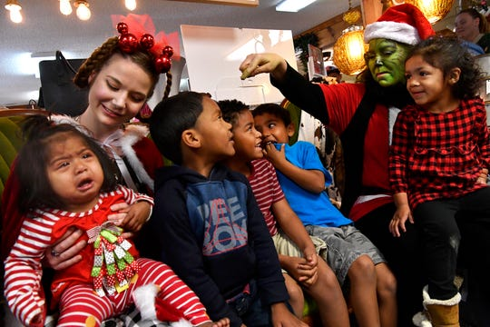 Cousins and siblings sit with the Grinch and Olivia Madden as Cindy Lou Who at Vickie's Gifts in Roscoe Saturday.