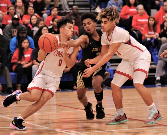 Abilene High's Jalen McGee, center, tries to knock the ball away from Cooper's Josh Henry, left, as Noah Garcia helps his teammate in the fourth quarter. Cooper beat the Eagles 78-74 in overtime on Friday, Dec. 20, 2019, at Cougar Gym.