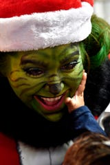 Emeri Dixon, 14 months-old, puts her hand to Carmen Hall's face, fascinated by Hall's Grinch makeup Saturday at Vickie's Gifts in Roscoe.