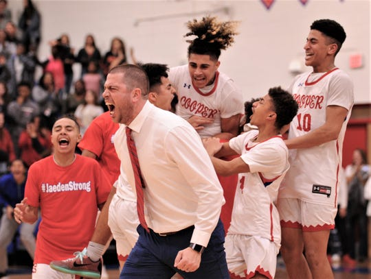 Cooper coach Bryan Conover, near left, and his Cougars celebrate their 78-74 overtime victory over Abilene High on Friday, Dec. 20, 2019, at Cougar Gym.