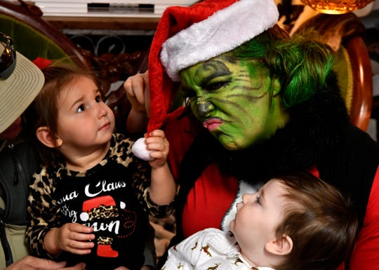 Steeley Singleton tugs on the Grinch's hat as her cousin Merritt Neff relaxes Saturday at Vickie's Gifts in Roscoe.