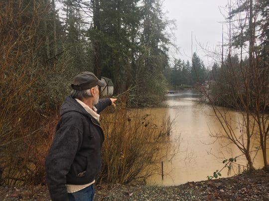 Bill Simmons points to where runoff from the Ridgeline construction site flowed across Baker Road an into Lake Emelia on Friday after heavy rains. Simmons and others in the Lake Emelia neighborhood have opposed the development since it was proposed in 2007.
