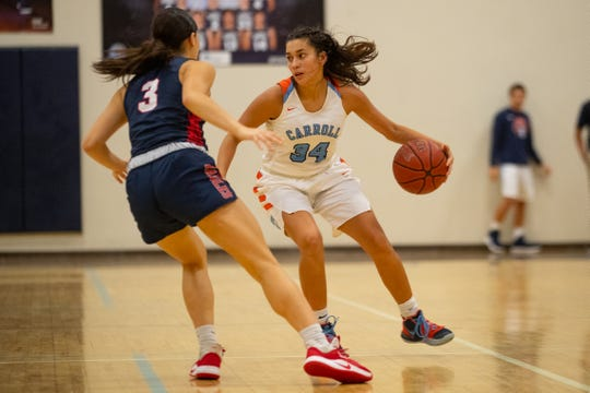 Carroll's Jolyssa Cortez drives the ball up the court as Veterans Memorial's Madison DeLosSantos gourds her during their game at Carroll High School on Friday, Dec. 20, 3019.