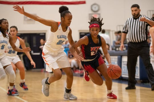 Veterans Memorial's Anaisja Banks drives the ball up the court as Carroll's Kaih Barron guards her during their game at Carroll High School on Friday, Dec. 20, 3019.
