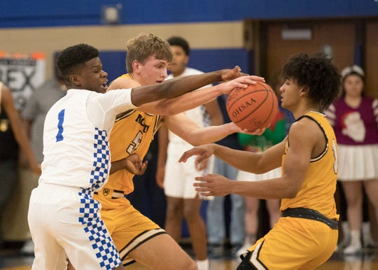 Logan Duncomb gets his hands on the ball near teammate Aidan Turner in Moeller's 78-51 win at Chillicothe High School Dec. 20, 2019.