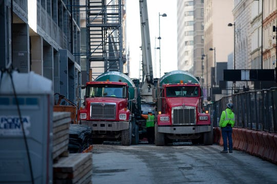 Trucks deliver concrete to the building being constructed near the intersection of Race and Fourth Streets in Cincinnati on Saturday, Dec. 21, 2019. The building partially collapsed on Monday, Nov. 25, 2019, killing one worker.