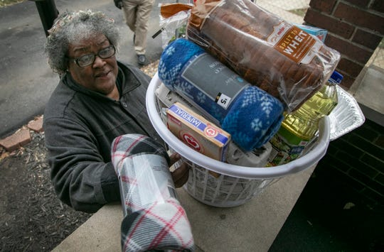 Patricia Ann Williams, 67, picks up a basket and some pork chitterlings to help get through the holidays thanks to Mama Tu-Tu (aka Wanda Beavers) who hands out toys and baskets of food to families in need in Jackson for the holidays Friday, Dec. 13, 2019.