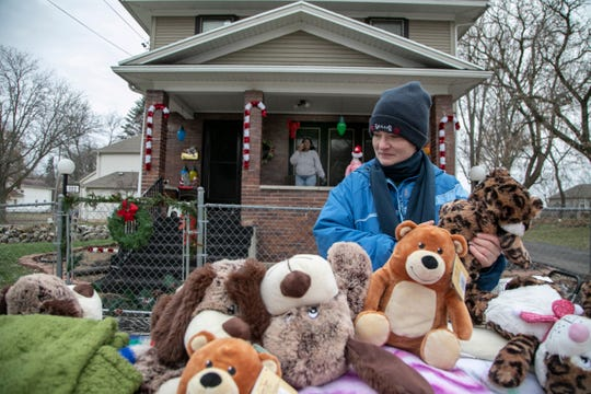 "A woman named Jennifer picks up a stuffed animal for her son outside of Mama Tu-Tu's house in Jackson Friday, Dec. 13, 2019. ""I love Mama Tu-Tu, she helps everyone"" said Jennifer."