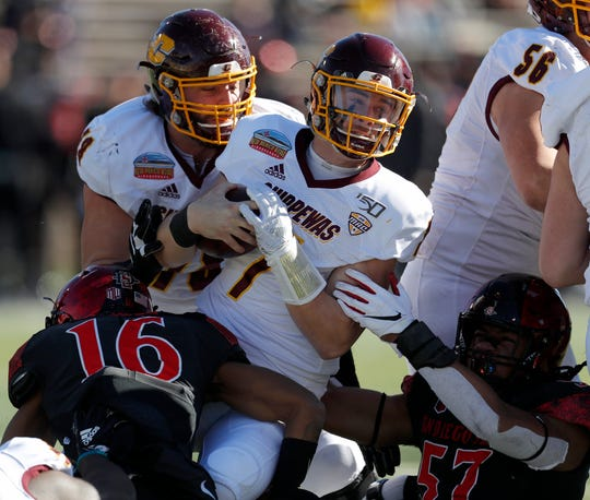 Central Michigan quarterback Tommy Lazzaro is sacked by San Diego State cornerback Luq Barcoo (16) and defensive lineman Keshawn Banks during the first half of CMU's 48-11 loss in the New Mexico Bowl on Saturday, Dec. 21, 2019 in Albuquerque, N.M.
