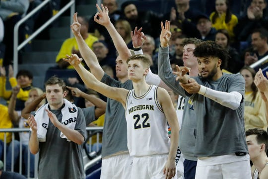Michigan guard Cole Bajema forward Isaiah Livers, right, celebrate a 3-point basket with teammates in the bench area during the second half of U-M's 86-44 win on Saturday, Dec. 21, 2019, at Crisler Center.