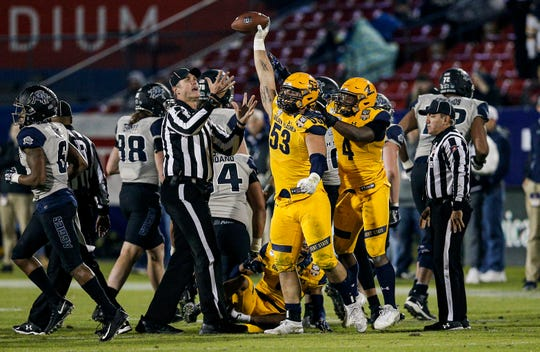 Kent State defensive end Alex Hoag (53) celebrates recovering a Utah State fumble during the second half.