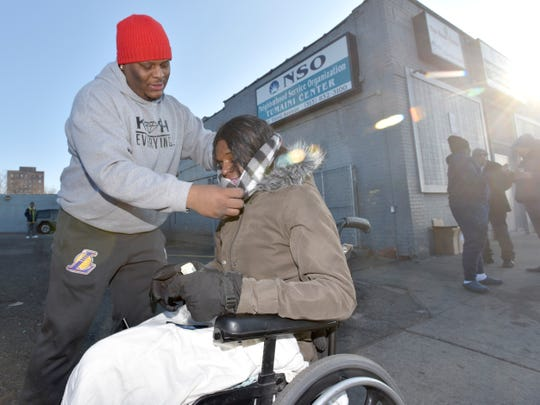 InKredible Solutions owner Marcus Gleaves helps Nina Nickerson, both of Detroit, with her new scarf during the 3rd annual Operation H.A.N.O (Help A Neighbor Out) in the parking lot of the NSO Tumaini Center, a nonprofit homeless-recovery facility, Saturday morning.