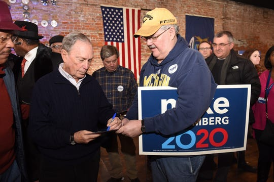 Democratic Presidential candidate Mike Bloomberg autographs a photograph for Larry Taylor at the opening of Bloomberg's Eastern Market campaign office in Detroit on Saturday, December 21, 2019.