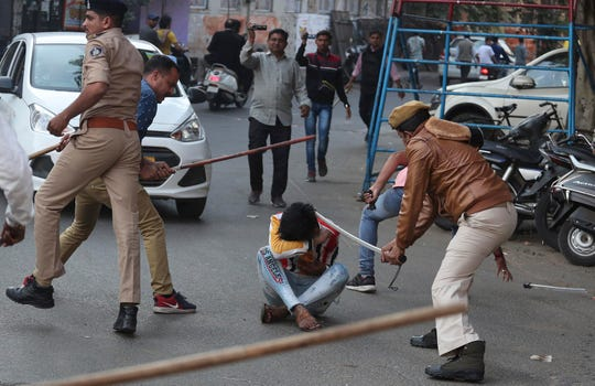 Indian policemen baton charge a man during a protest against a new citizenship law in Ahmadabad, India, Thursday, Dec. 19, 2019.