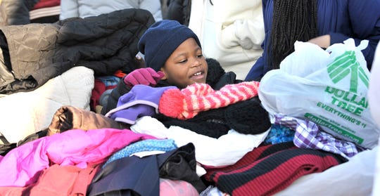 Rriana Lyle, 5, of Detroit, looks at winter accessories at the NSO Tumaini Center on Saturday.