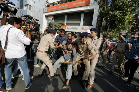Indian police detain a man during a protest against a new citizenship law in Ahmadabad, India, Thursday, Dec. 19, 2019.