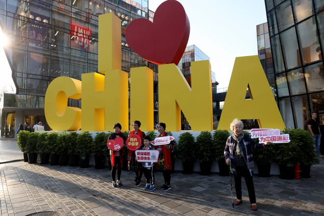 """FILE - In this Oct. 7, 2019, file photo visitors hold up patriotic slogans including """"Cheer for China"""", """"My China Dream"""" near an I Heart China art installation in Beijing."""