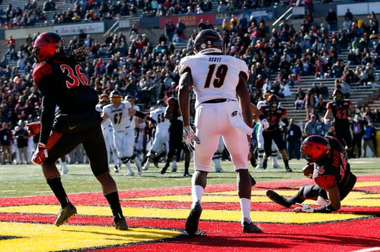 San Diego State cornerback Luq Barcoo (16) intercepts a pass intended for Central Michigan wide receiver Tyrone Scott (19) in the end zone during the first half.
