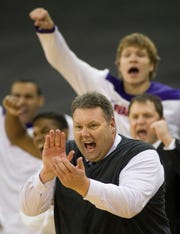 Purple Aces coach Marty Simmons and his bench erupt after another big basket during the first half of their game against the Valparaiso Crusaders at the Ford Center Wednesday night, Nov. 21, 2013.