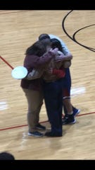 The Green family embraces following George's surprise return during Thursday night's girls basketball game between Tecumseh and Tell City.