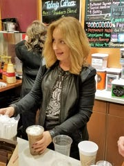 Manager Elaine Creamer serves a frothy espresso drink at Beans and Baristas.