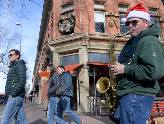 Michael Brown, a musician in the nationally known oldies band Sha Na Na, busks in Old Town in Fort Collins, Colo. on Friday, Dec. 20, 2019.