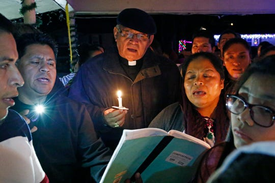 Cardinal Alvaro Ramazzini of Guatemala, back center, sings as he participates in La Posada, with parishioners of St. Anne Catholic Church in Carthage, Miss., Friday night, Dec. 20, 2019, following a listening session with immigrants impacted by the Aug. 7 arrests by immigration agents at seven Mississippi food processing plants.  (AP Photo/Rogelio V. Solis)