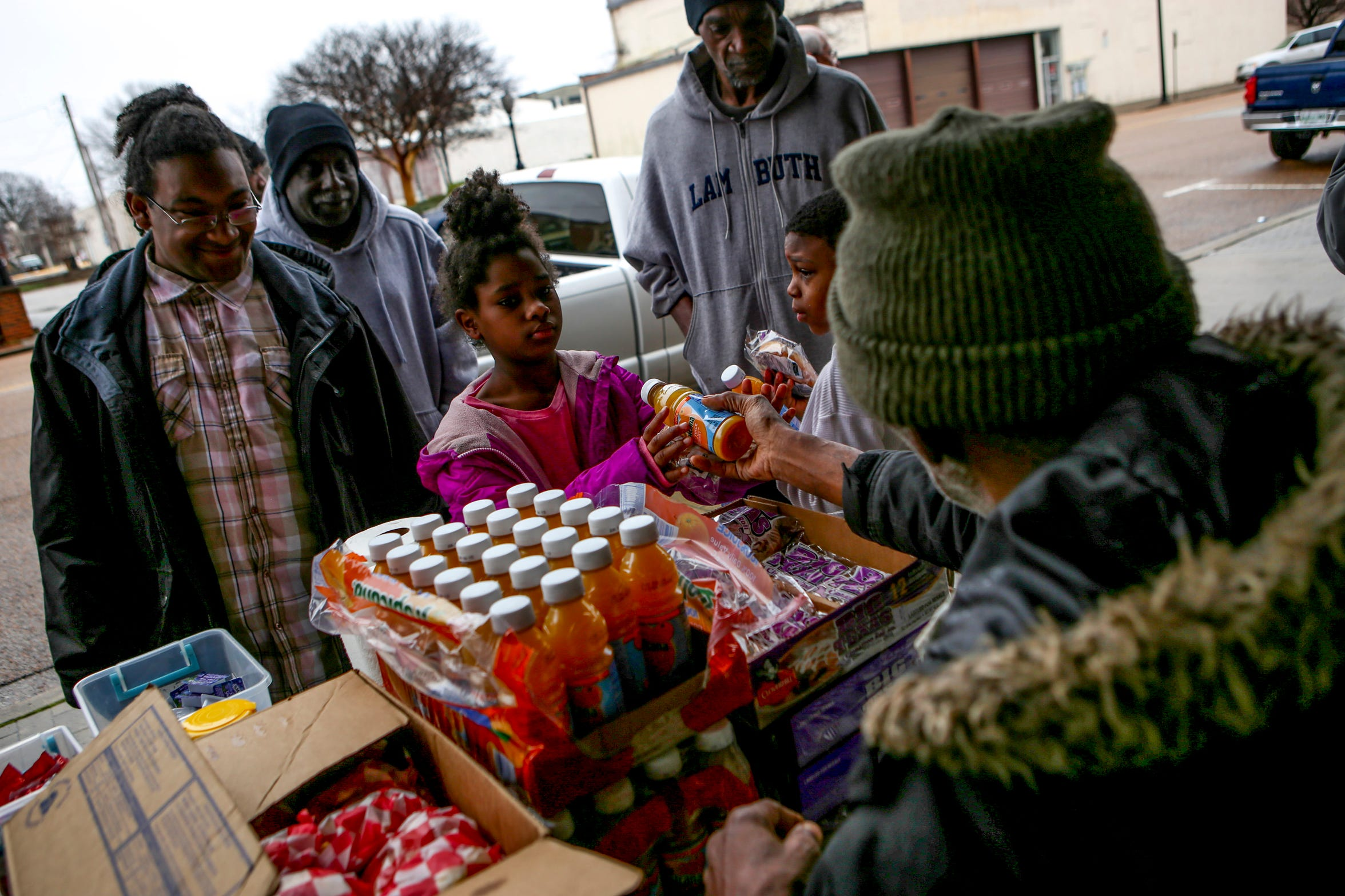 Robert Wynne hands out orange juice and breakfast meals to anyone in line waiting for food at the Church Without Walls at the intersection of Church and College in Jackson, Tenn., on Sunday, Feb. 17, 2019.