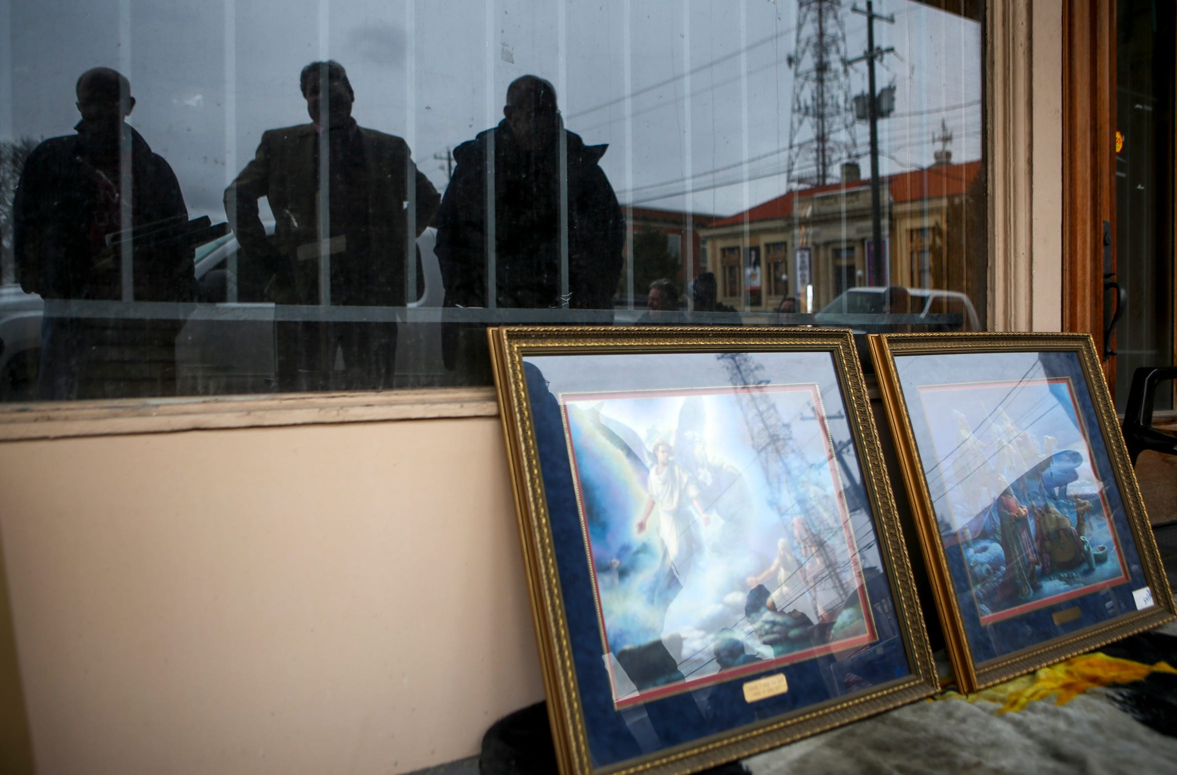 Pat Parham, left, brother Jerry, center, and brother Ben, right, reflected in a glass window, admire paintings Jerry brought for their Christmas service at the Church Without Walls at the intersection of Church and College in Jackson, Tenn., on Sunday, Dec. 23, 2018.