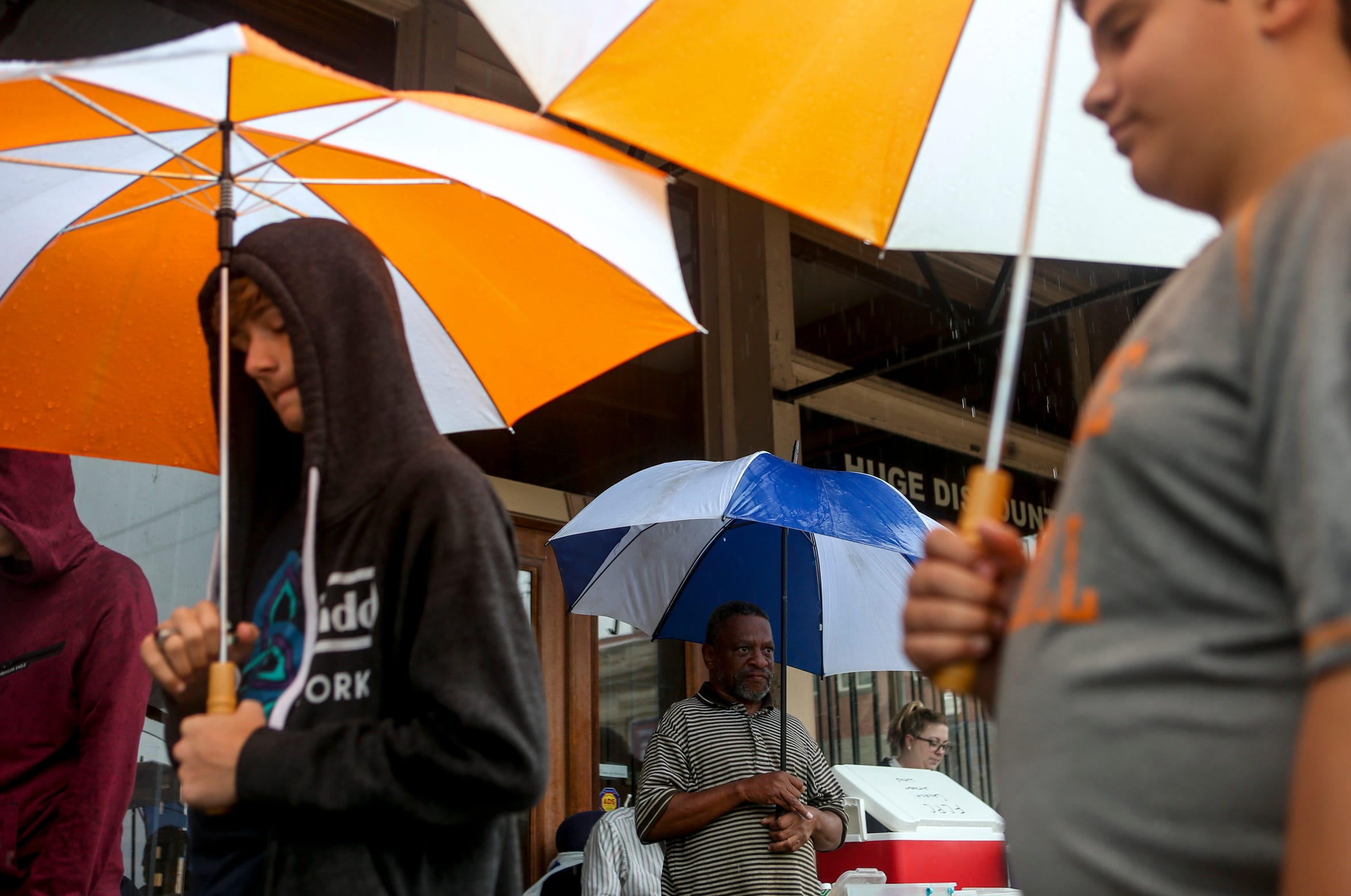 Attendees and volunteers at the Church Without Walls stand in the rain during service at the intersection of Church and College in Jackson, Tenn., on Sunday, Sept. 9, 2018.