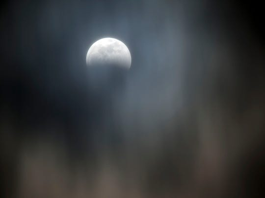 Clouds pass under the moon during a penumbral eclipse at 9:55 pm. on Sunday, January 20, 2019.