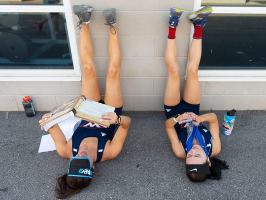 West High School runner Janie Holecek studies for her AP European history class as she and teammate Hannah Burkhart rest their legs after they helped win the 4x800 meter relay at the KIL Championships at Hardin Valley Academy on Tuesday, April 30, 2019.