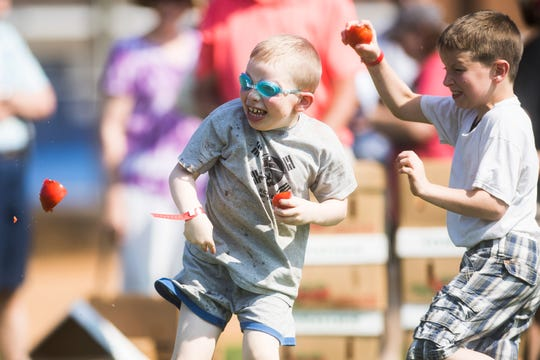 At left Joseph Godeicke, 6, of Washburn, attempts to dodge a tomato during the tomato wars at the annual Grainger County Tomato Festival in Rutledge, Tenn. Saturday, July 27, 2019.