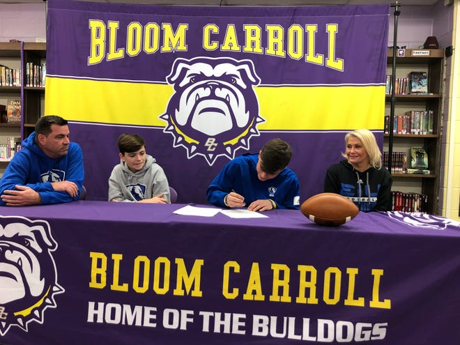Bloom-Carroll senior Otto Kuhns signs his national letter of intent to continue his education and play football at Eastern Illinois. Seated with Kuhns is his father, Eric, brother, Holdyn and mother, Aisha.
