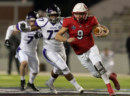 North Central quarterback Broc Rutter runs past UW-Whitewater defensive linemen Jermaine Copeland during the NCAA Division III championship game Friday in Shenandoah, Texas.