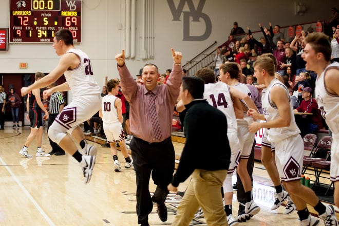 Wes-Del players and coaches celebrate following their 72-69 overtime victory over Wapahani at Wes-Del High School Dec. 20, 2019.