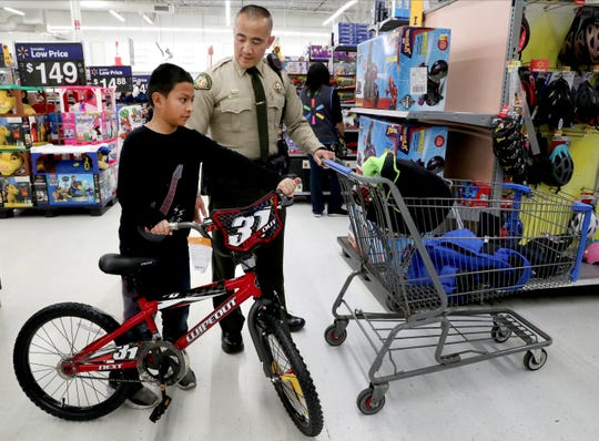 Williamson County Sheriff's Deputy Mon Sirivong helps Aaron Cervants, 9 pick out presents during Smyrna's Cops and Kids event on Saturday Dec. 21, 2019, at the Smyrna Walmart.