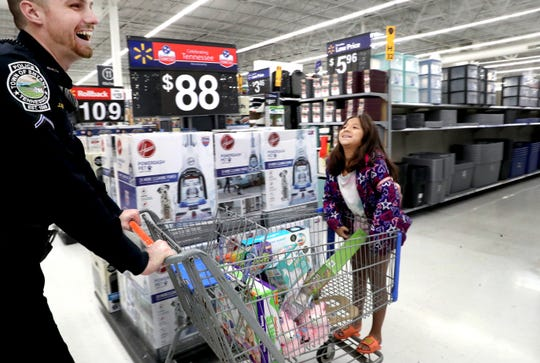 Beyonce Jimenez, 9 rides on the front of the cart as she shops with Smyrna Officer Jonathan Beverly during Smyrna's Cops and Kids event on Saturday Dec. 21, 2019, at the Smyrna Walmart.