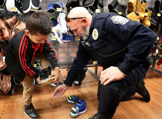 Smyrna K-9 Officer Don Godby helps Geanri Jimenez, 5 pick out shoes during Smyrna's Cops and Kids event on Saturday Dec. 21, 2019, at the Smyrna Walmart.
