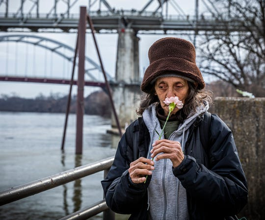 LuAnn Nicholas honors the memory of her friend Nina Page during a flower ceremony that was part of the 2019 Annual Homeless Memorial Saturday, December 21, 2019 at Riverfront Park.