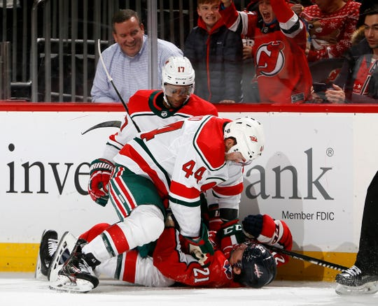 Miles Wood #44 of the New Jersey Devils checks Garnet Hathaway #21 of the Washington Capitals as Devils' Wayne Simmonds #17 watches in the second period of an NHL hockey game on Dec. 20, 2019 at Prudential Center in Newark, New Jersey.