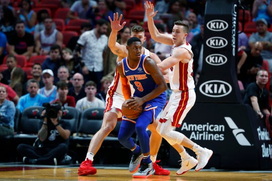 New York Knicks forward RJ Barrett (9) looks for an opening past Miami Heat forwards Duncan Robinson, right, and Meyers Leonard, rear, during the second half of an NBA basketball game Friday, Dec. 20, 2019, in Miami. The Heat won 129-114.