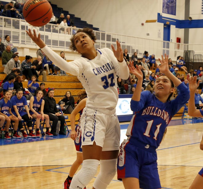 Carlsbad's Allie Myers (32) gets a rebound over Las Cruces' DeAnna Sifuentes (11) in the first half of their game on Dec. 20, 2019. Carlsbad won, 56-21.