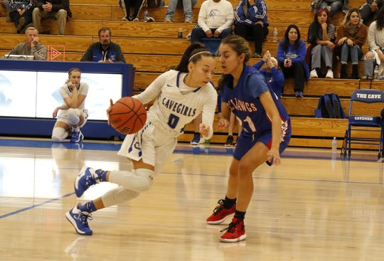 Carlsbad's Baylee Molina drives by Las Cruces' Shooty Molinar in their game on Dec. 20, 2019.