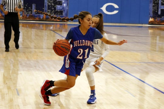 Las Cruces' Shooty Molinar drives by Carlsbad's Baylee Molina on Dec. 20, 2019. Carlsbad won, 56-21.