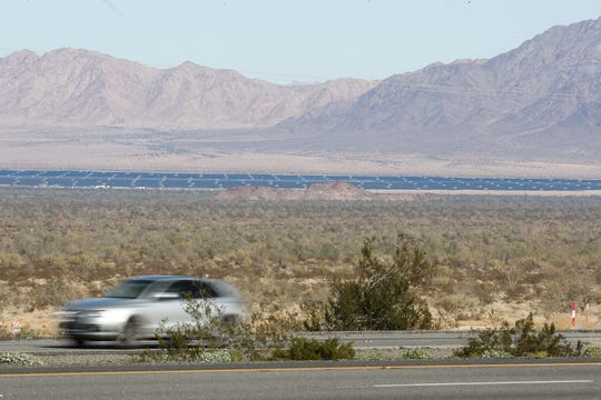 A car travelling along I-10 passes in front of the solar panels at Desert Sunlight Energy Center, which is several miles away, December 19, 2019.