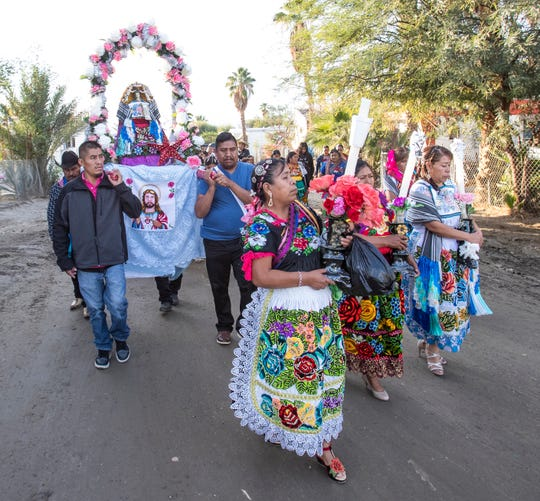 Florinda Gonzalez leads a procession with Purepechas at the Oasis Trailer Park carrying an image of the Virgin of Guadalupe on December 12, 2019 The Purepechas were headed to Our Lady of Guadalupe Catholic Church in Mecca, California.