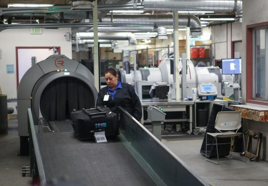 A TSA security officer inspects baggage at the Palm Springs International Airport, December 6, 2019.  This area will be renovated in the near future.