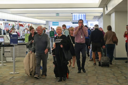Travelers pass through a narrow area near check-in that will be widened during upcoming renovations at Palm Springs International Airport, December 20, 2019.